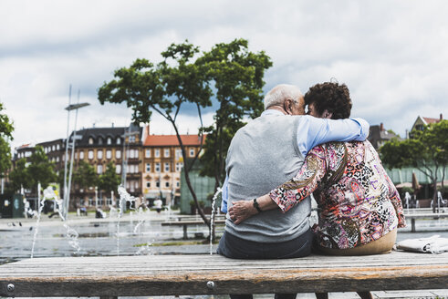 Germany, Mannheim, back view of kissing senior couple sitting on a bench hugging each other - UUF008073