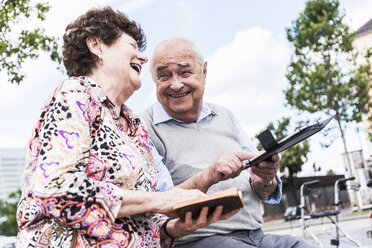 Laughing senior couple sitting together on a bench with book and tablet - UUF008076
