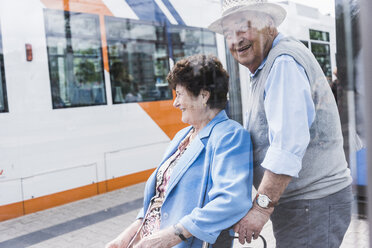 Germany, Mannheim, happy senior couple with wheeled walker waiting at station - UUF008079