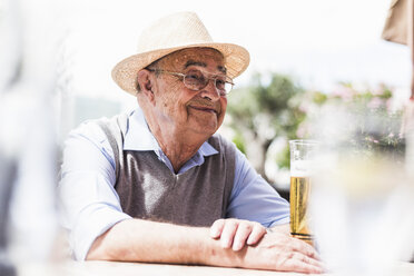 Portrait of happy senior man drinking glass of beer in a sidewalk cafe - UUF008082