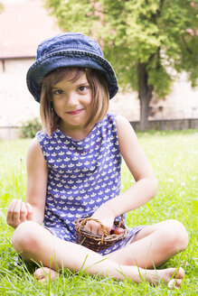 Portrait of little girl sitting on a meadow with basket of gooseberries - LVF005116