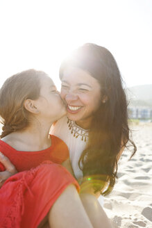 Little girl kissing her mother on the beach - VABF000680