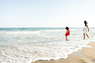 Little girl and her mother walking at seafront on the beach - VABF000683