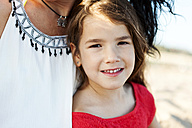 Portrait of smiling little girl besides her mother on the beach - VABF000695