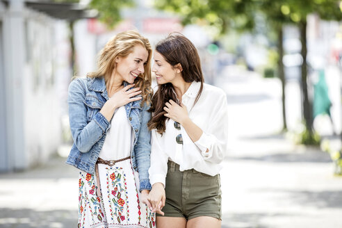 Two smiling young women walking and talking - GDF001040