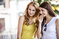 Two smiling young women talking and looking at shop window - GDF001043