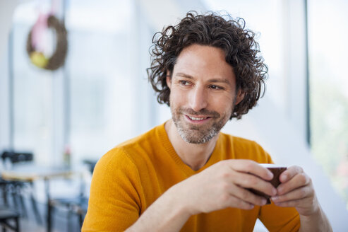 Portrait of smiling man with curly brown hair holding cup of coffee - DIGF000569