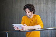 Man with curly brown hair leaning on railing looking at tablet - DIGF000575