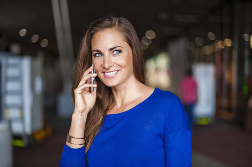 Smiling brunette woman on cell phone - DIGF000586