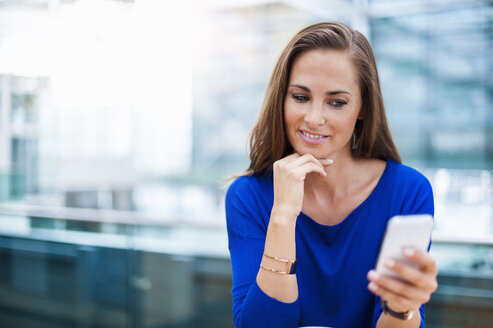 Smiling brunette woman looking at cell phone - DIGF000589