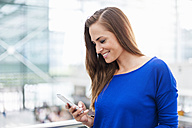 Smiling brunette woman looking at cell phone - DIGF000592