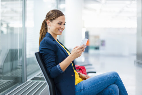 Smiling woman sitting on chair looking at cell phone - DIGF000613