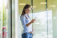 Smiling brunette woman looking at cell phone - DIGF000628