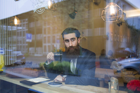 Fashionable man with beard sitting in coffee shop, drinking coffee - NAF000011
