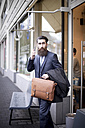 Hipster with briefcase and smart phone leaving coffee shop - NAF000014