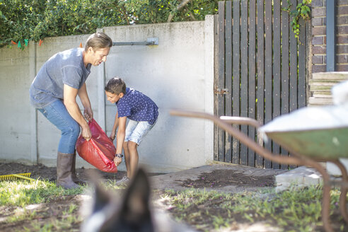 Father and son working together in garden - ZEF008992