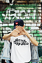 Young man wearing t-shirt with saying 'Hotter Than Hell' hiding face behind his hands - JUBF000166