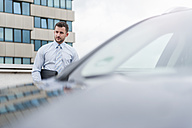 Businessman at car on parking lot - DIGF000642