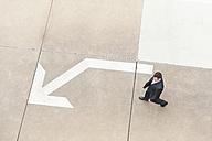 Businessman walking on paving with large arrow - DIGF000660