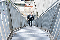 Businessman walking upstairs - DIGF000663