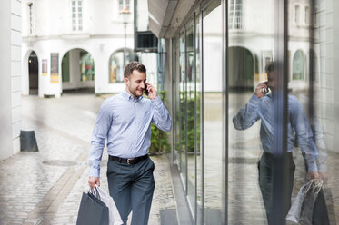 Young man with shopping bags on the phone passing a shop - DIGF000681