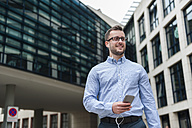 Smiling young man with cell phone and earbuds outdoors - DIGF000687