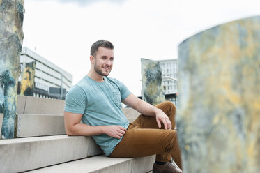 Smiling young man outdoors sitting on stairs - DIGF000693