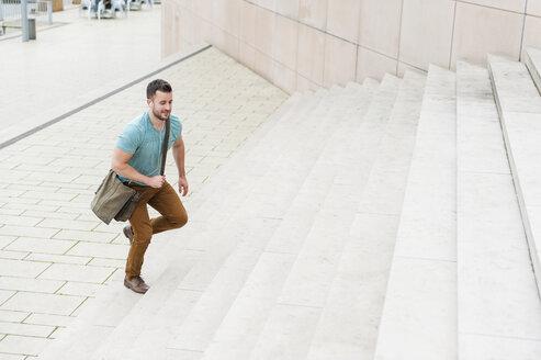Young man walking upstairs - DIGF000696