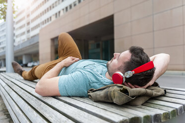 Relaxed young man lying on bench listening to music - DIGF000699