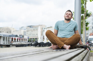 Relaxed young man outdoors sitting on bench - DIGF000705