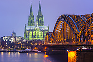 Germany, Cologne, view to lighted Cologne Cathedral with Hohenzollern Bridge in the foreground - WGF000888