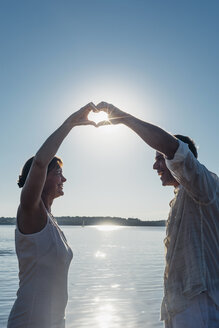 Couple standing at Lake Cospuden, forming heart with hands against the sun - MJF001974
