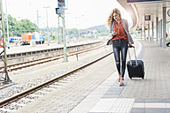 Young woman with wheeled luggage looking at her smartphone while walking at platform - DIGF000711