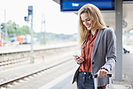 Smiling young woman at platform looking on cell phone - DIGF000714