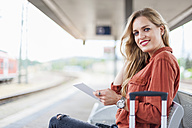 Portrait of smiling young woman with tablet sitting on bench at platform - DIGF000717