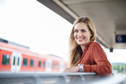 Portrait of smiling young woman sitting at platform - DIGF000720