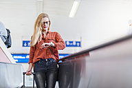Young woman standing on escalator of train station checking the time - DIGF000723