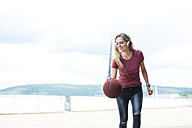 Smiling young woman with headphones playing with basketball on roof terrace - DIGF000732