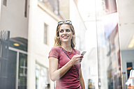 Portrait of smiling woman with smartphone standing in front of shop window - DIGF000738