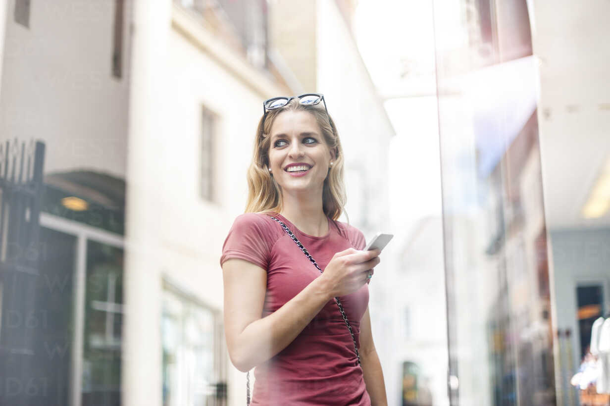 Portrait of smiling woman with smartphone standing in front of shop window - DIGF000738 - Daniel Ingold/Westend61