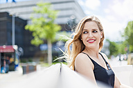 Portrait of smiling young woman sitting on a bench watching something - DIGF000750