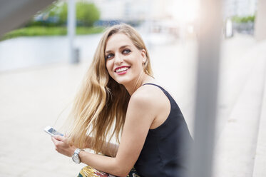 Portrait of smiling young woman with cell phone - DIGF000753