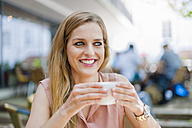 Portrait of smiling woman sitting in a sidewalk cafe with cup of coffee - DIGF000762