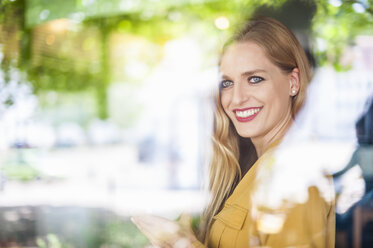 Portrait of smiling woman sitting behind window in a coffee shop - DIGF000765