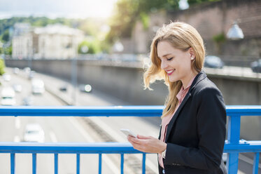 Smiling businesswoman on a bridge looking at her smartphone - DIGF000768
