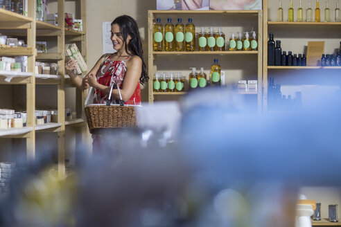 Woman taking product from shelf in health shop - ZEF009094