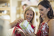 Two happy women with gift box in shop - ZEF009109
