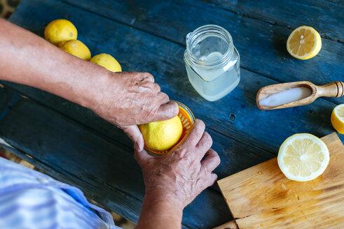 Close-up of hands squeezing lemons to make lemonade - KIJF000584
