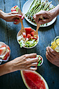 Close-up of hands eating salad, watermelon, lemonade, asparagus and candy - KIJF000596