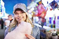 Young woman at fun fair eating candy floss - PES000242